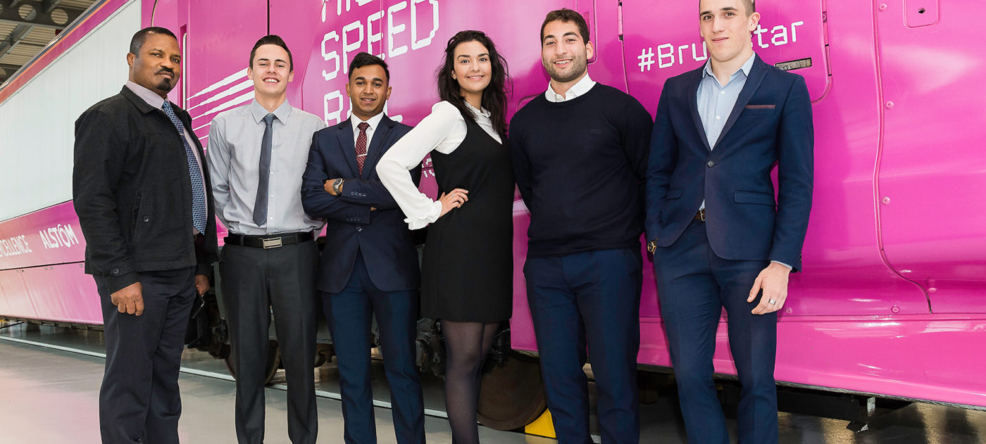 HS2 apprentices posing in front of a mock high speed train