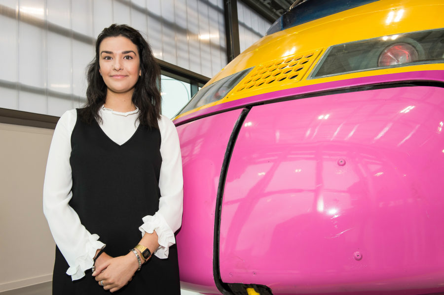 Clara standing next to a high speed train model at the National College of High Speed Rail