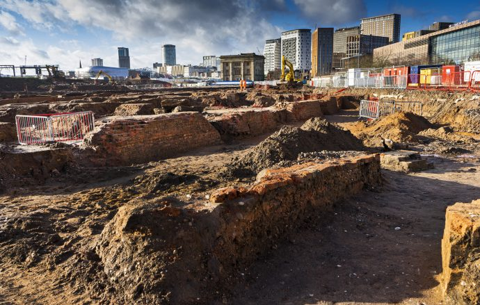 archaeological dig showing old foundations with Birmingham skyline in the background