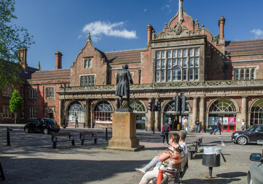 View of people sat on benches outside of Stoke railway station.